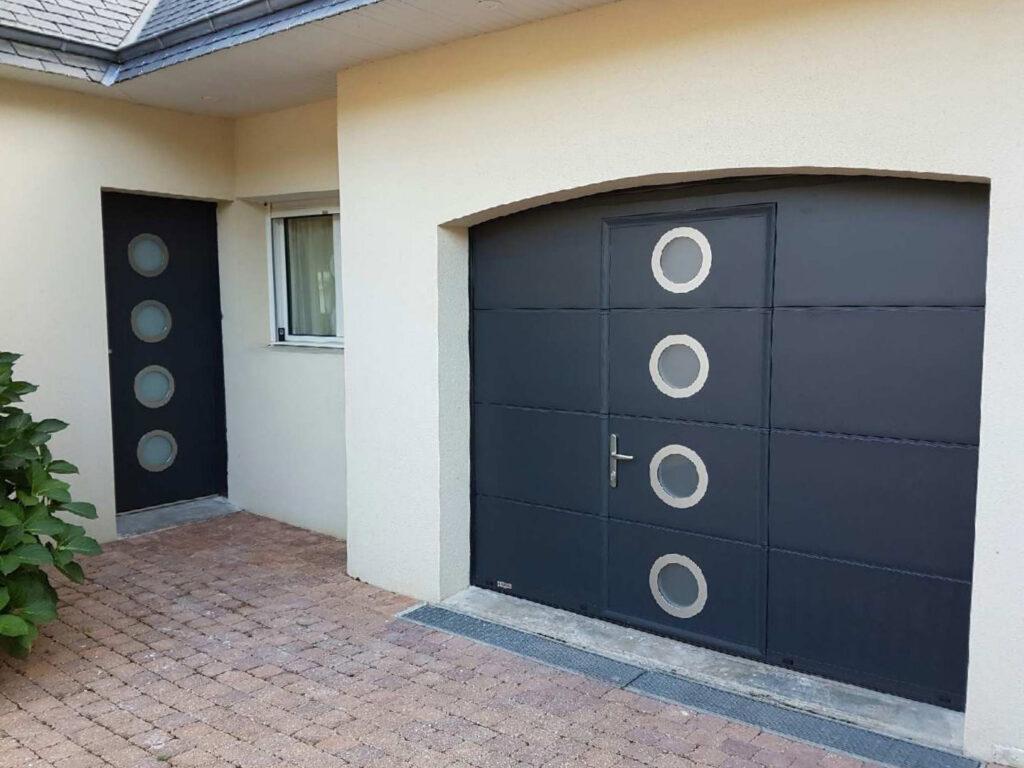 porte de garage sectionnelle gris anthracite avec hublots assortie à la porte d'entrée sur une maison neuve